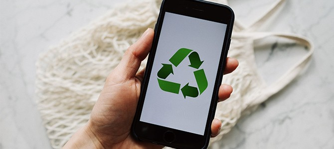 someone holding a smartphone with the recycling logo