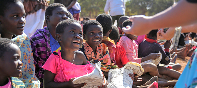 A group of Malawi children sit on the ground holding bags of Nu Skin VitaMeal.