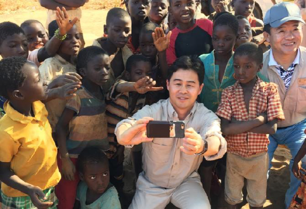 Nu Skin employee takes a selfie with a large group of Malawi children behind him posing for a picture.