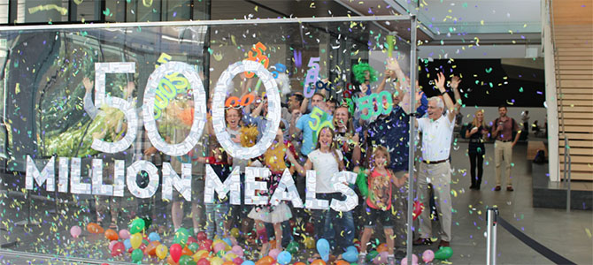 Nu Skin employees and their families pose for a picture to celebrate the donation of 500 million meals through the Nourish the Children initiative.