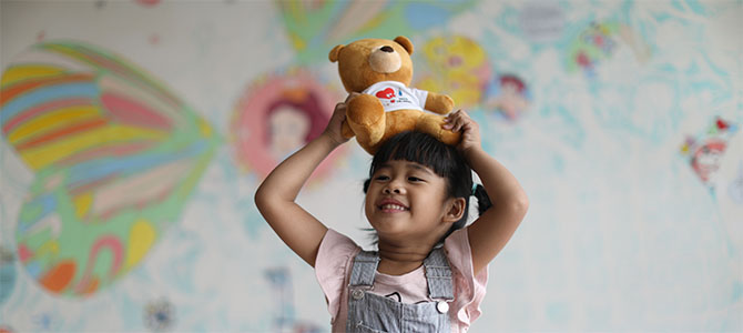 Yu-Jie smiles as she plays with a teddy bear.